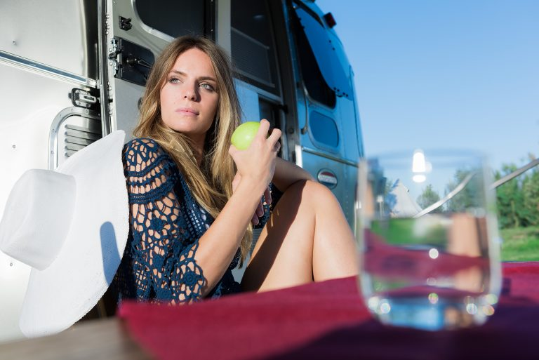 girl eating an apple outside an airstream